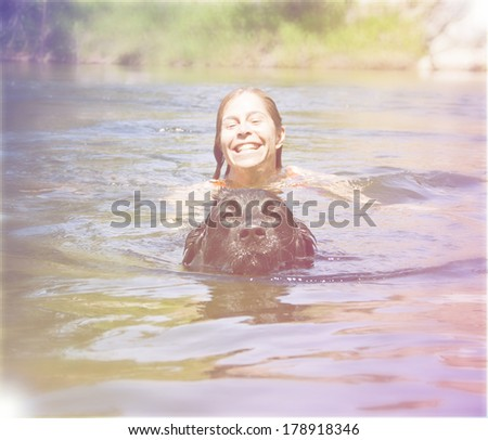 a girl and a big lab dog swimming in the water done with a retro - stock photo