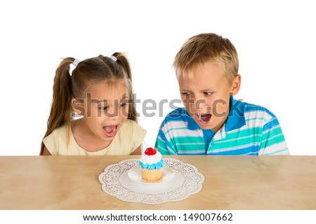 A girl and a boy are looking with excitement at a single delicious cupcake - stock photo