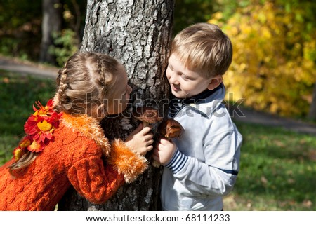 a girl and a boy are playing hide-and-seek in an autumn park - stock photo