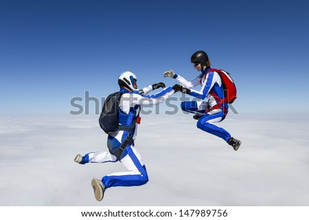 A girl and a guy skydivers perform pieces in free fall. - stock photo