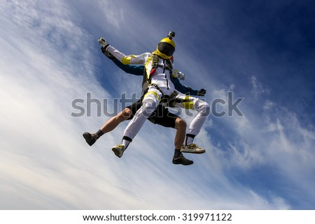 A girl and a guy skydivers perform pieces in free fall.