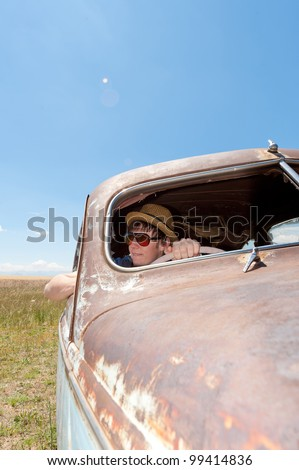 a girl and guy in old rusty car - stock photo
