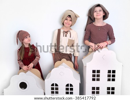a girl and two boys posing in toy houses - stock photo