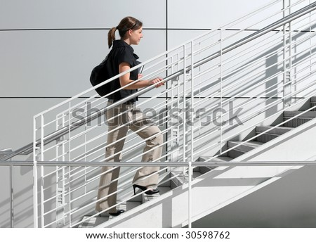 A girl college student walking up the staircase - stock photo