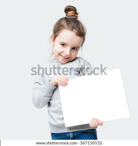 A girl coyly flirtatiously looking at the camera. Embarrassing. Holding white banner for your text advertising information. Gray background - stock photo