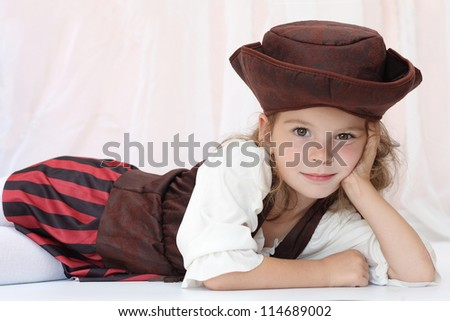 A girl dressed as a pirate lying on background - stock photo