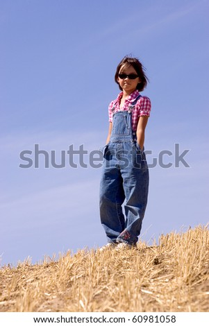 A girl dressed in overalls stands in a harvested wheat field. - stock photo