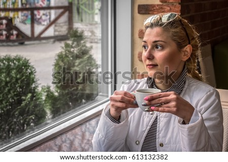 A girl drinks coffee in a restaurant and looks out the window