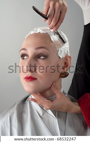A girl during shaving off her hair by cutthroat - stock photo