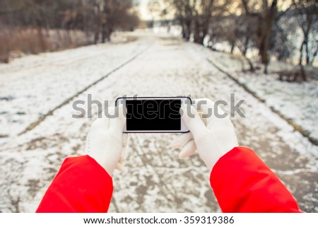 a girl gets on the hip a mobile telephone on a background a winter street - stock photo
