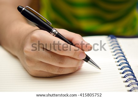 A girl hand is holding a pen and writing on a book