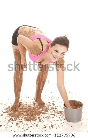 A girl having some fun reaching in a bucket of mud. - stock photo