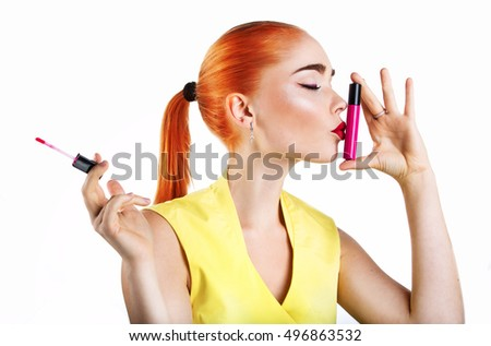 A girl holding a lipstick isolated on white background