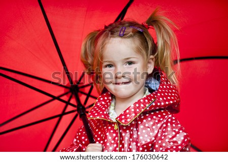 A girl holding a red umbrella that is open. - stock photo