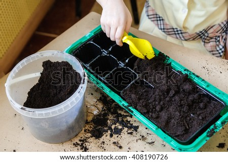 A girl holding a yellow shovel over green tray with black soil - stock photo