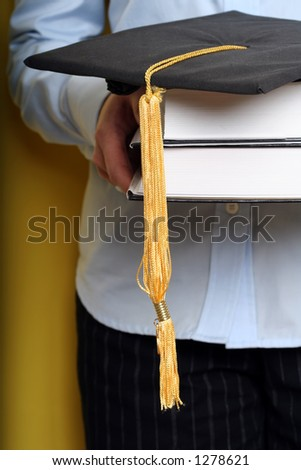 A girl holding books and graduation cap - stock photo