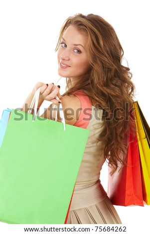 A girl holding paper bags, looking at camera and smiling - stock photo