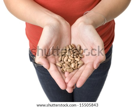A girl holds a handfull of beans - stock photo