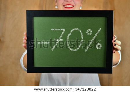 a girl holds a sign saying sale - 70 percent - stock photo