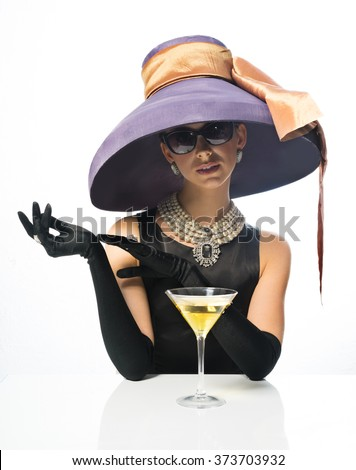 A girl in a big hat and sunglasses, like a movie star, drinking martinis