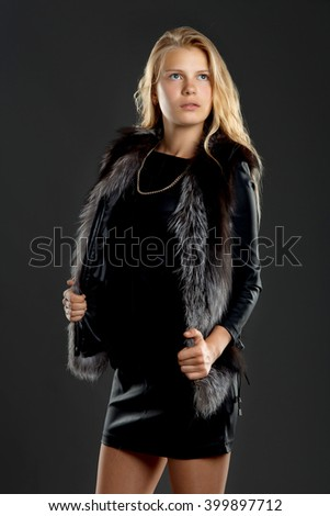 a girl in a black leather dress and with gray mink vest
