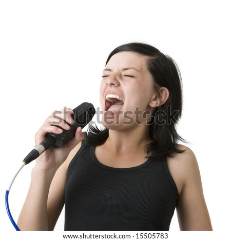 A girl in a black shirt sings loudly into a mic - stock photo
