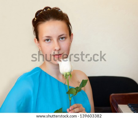 A girl in a blue dress with a flower in her hand after a concert of classical music - stock photo