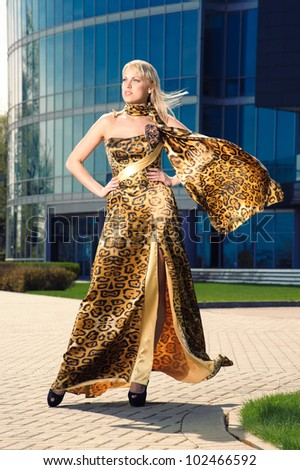 A girl in a gold silk dress on the streets of the city - stock photo