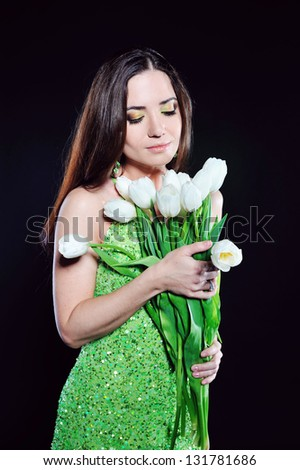 A girl in a green dress with white tulips - stock photo