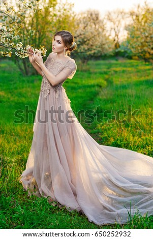A girl in a long beige dress posing in the garden of blooming trees
