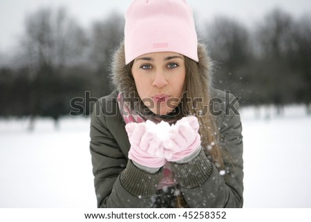 A girl in a park in the jacket blows snow from the palms