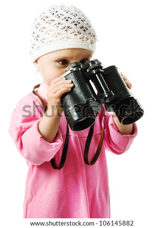A girl in a pink dress with a pair of binoculars on a white background. - stock photo