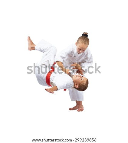 A girl in a white clothes with a boy with red belt are training throw - stock photo