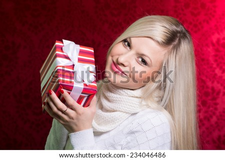 A girl in a white sweater and striped gift with white bow looking at the camera. Close-up portrait of a beautiful young woman on a red background. Holiday Sale