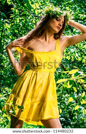 A girl in a yellow dress in the forest - stock photo