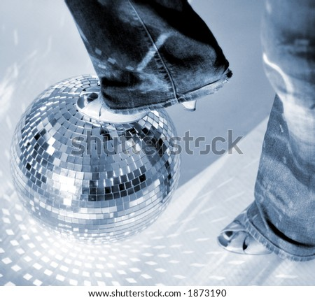a girl in jeans resting foot on a glitterball like a football