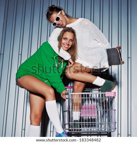a girl in sunglasses holding a skateboard is hugging a girl in a green hoodie and roller skates  - stock photo