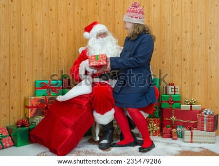 A girl in winter clothing visiting Santa in his grotto - stock photo