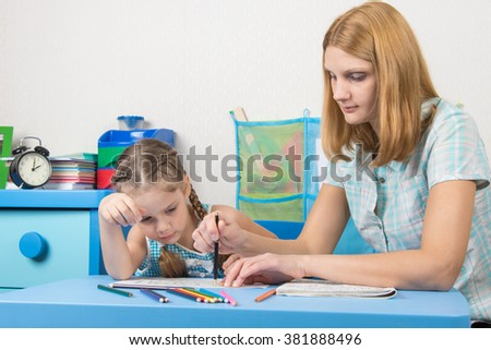 A girl interested look like mom paints a stencil - stock photo