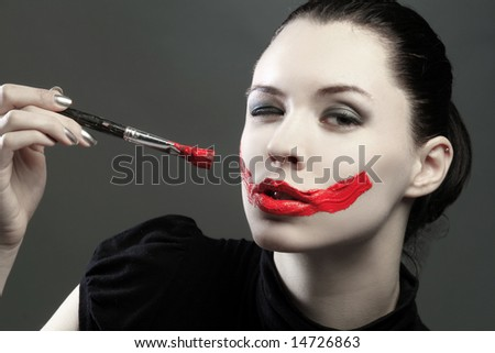 a girl is blinking and painting herself - stock photo