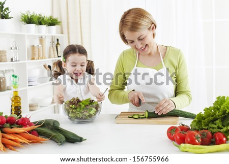 A girl is helping to her mom, while she work something else - stock photo