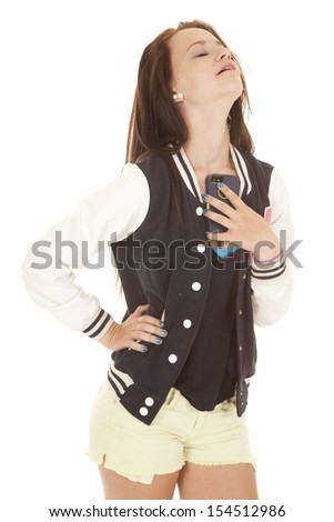 A girl is holding her phone by her chest. - stock photo