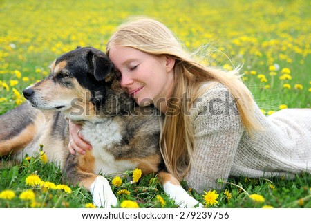 A girl is laying outside in the grass, tenderly hugging her aging German Shepherd mix dog with her eyes closed.