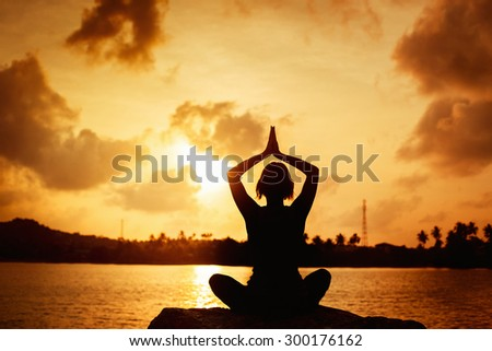 A girl is meditating on a stone at seashore at golden sunrise background.