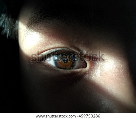 A girl is staring straight behind the shadow of  the sunlight. Low light. - stock photo