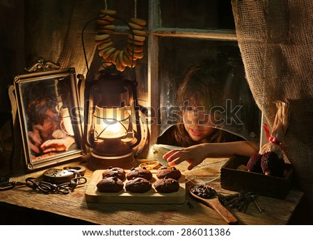 A girl is trying to steal cookies from a witch  - stock photo