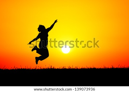 A girl jumping up in the air on top of a hill in front of a blood red sunset. - stock photo