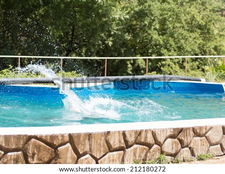 A girl jumps from a diving platform into the pool - stock photo