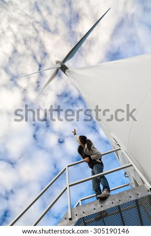 A girl looks a wind turbine from the below. The perspective of the image gives the sensation of how much is big that green-energy generator. - stock photo
