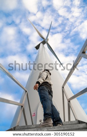 A girl looks a wind turbine from the below. The perspective of the image gives the sensation of how much is big that green-energy generator.